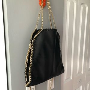 Black faux leather purse with gold chains